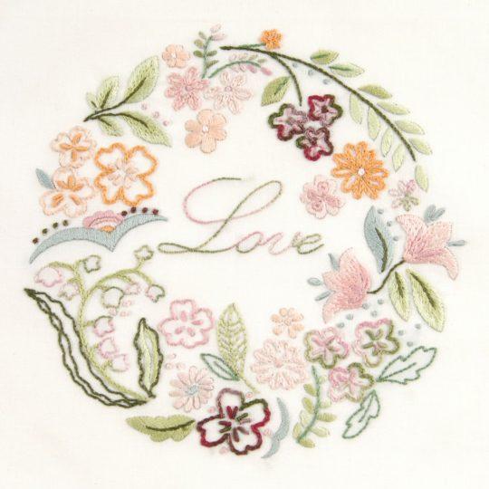 Sticken: Blumenkranz mit Blättern und dem Wort Love | bedruckter Stoff