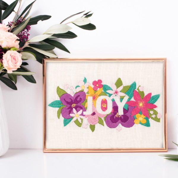 Buntes Blumenbild mit dem Wort Joy sticken | Stickpackung über Zur Lila Pampelmuse